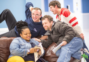 3 people supported by Penn-Mar and a team member on a couch reading and smiling